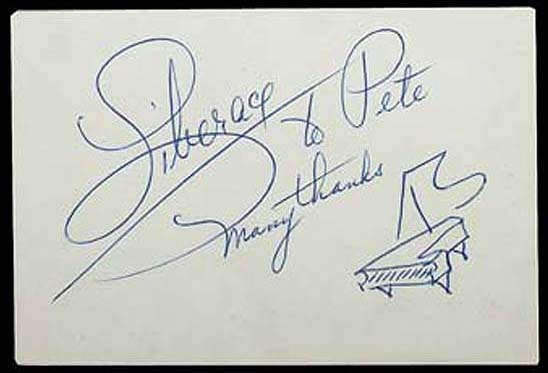 A card signed by Liberace with his distinctive signature and grand piano sketch