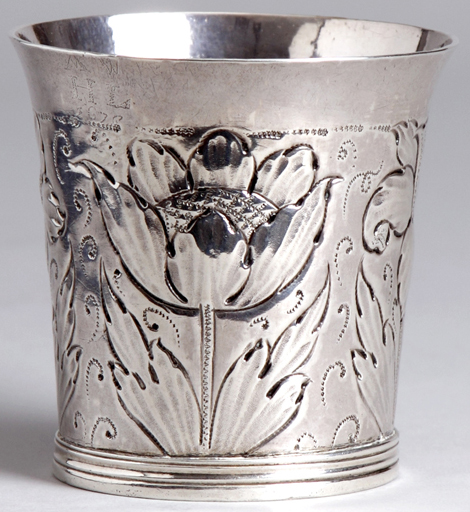 A 17th century English silver beaker with embossed flowers and leaf decoration