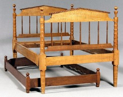 A Tennessee Sheraton tiger maple bedstead, highly figured maple with poplar secondary, head and footboards with pitched pediments and finely turned posts; together with a walnut and cherry trundle bed
