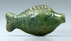 A two-sided Moravian fish flask, green-glazed cream-colored earthenware, molded with scales, fins and eyes, attributed to Rudolph Christ, Salem, North Carolina, early 19th century.