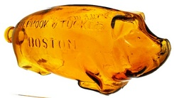 bottles, flasks & jars, Massachusetts, A 'SUFFOLK BITTERS PHILBROOK & TUCKER BOSTON' figural pig bitters bottle with applied double collar. Dazzling color in a brilliant yellow, orange and plenty of whittle.