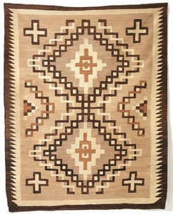 A Navajo Crystal weaving, two shades of brown and cream, with two large diamonds at center, surrounded by four large diamonds and a sawtooth border.