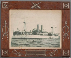 An early 20th century painted sheet iron frame made from remnants of the battleship Maine with photograph