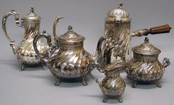 A French Rococo silver tea and coffee service with spiral ribbed pyriform, tab feet; consisting of teapot, coffeepot (6556), creamer (6559), covered sugar bowl, chocolate pot with wood handle side.