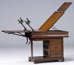 W. D. Allison Company Medical Examination Table, Walnut Reclining Table  With Cabinet Base; Image Credit On Full Record.