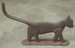 A cast iron boot scraper, unattributed, in the form of a cat with [long tail and] traces of black paint.