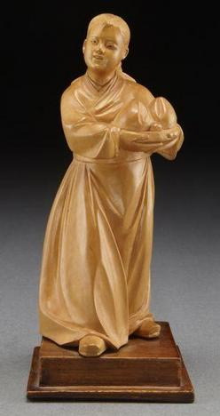 A circa 1960 Chinese Cultural Revolution carved boxwood figure, depicting a Mongolian girl holding two peaches.