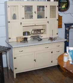 A Hoosier-style kitchen cabinet with etched glass doors, white paint and a graniteware work surface; image credit on full record.