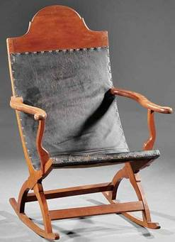 Furniture: A Louisiana carved cherrywood campeche rocking chair, early 19th century, distinctive architectural half-round crest, continuous back and seat with leather [sling] upholstery and nailhead trim, serpentine arms and supports over curule rocker base, pegged and tenoned construction.