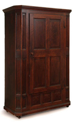 Furniture: A carved schrank, Zoar, Tuscarawas County, Ohio, mid 19th century, cherry, walnut, and poplar. One-piece [wardrobe],with [molded cornice], canted and carved pilasters, paneled door, and diamond panels below the door. Interior with carved hooks and a shelf.
