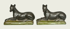 A very rare and important pair of Shenandoah Valley redware [dog figures depicting] whippets, both signed Samuel Bell / Winchester Sept 21 1841, Winchester, Virginia origin, matched pair of molded redware whippet figures with incised details to face and paws, both dogs painted black with white-and-red eyes and red mouths, reclining atop green-painted bases with incised borders.